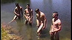 Four young studs take a swim in the lake and stroke their big cocks