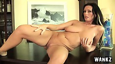 Buxom cougar with sexy legs Pandora drives a long glass dildo in and out of her cunt