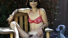 Skinny Asian MILF bares her bush while sucking on a glass toy