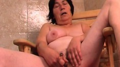 Kinky mature lady satisfies her sexual urges with a dildo in the sauna