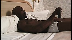Black stud lies on the bed and strokes his massive shaft to pleasure