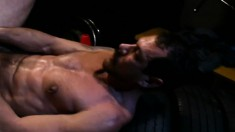 Bearded stud crouches to lick a hunk's cock and fuck him in the ass with his fist